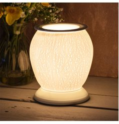 A beautifully detailed ceramic based aroma lamp featuring a woodland tree inspired embossed design and warm glowing LED