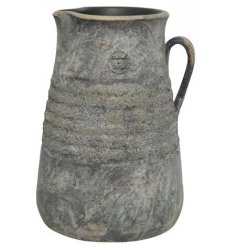 An overly distressed terracotta based jug set with a ridged central decal, tarnished colour and handle