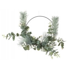 A large half wreath decorated with green leafs, white berry foliage and eucalyptus