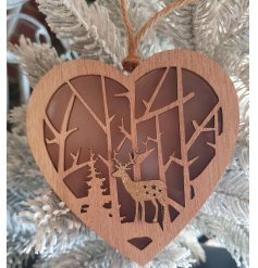 A charming wooden hanging heart with a cut out woodland scene centre and illuminating warm glow from within