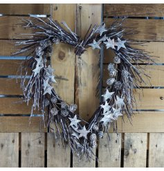 A natural twig wreath in a heart form, set with added pinecones, stars and glitter