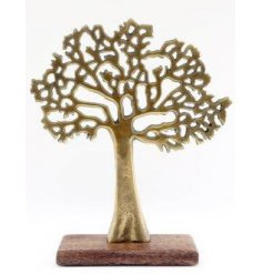 An antique gold toned Tree Ornament set upon a natural wood block base