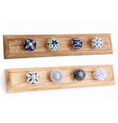 A natural wooden block base set with assorted green, white and blue ceramic knobs