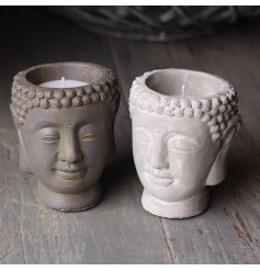 A mix of decorative buddha head candle pots with overly distressed charms and features