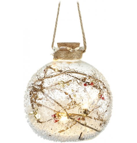A rough ridged glass bauble filled with assorted twigs, berries and a warm glowing LED display