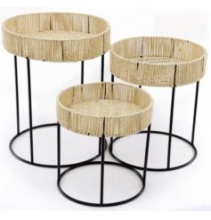 Assorted by their alternate sizes, these simple themed geometric wire based tables each feature a woven straw top