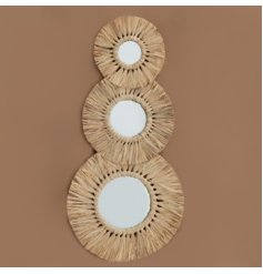 A set of 3 assorted sized mirrors decorated with a dried grass surround and circular design