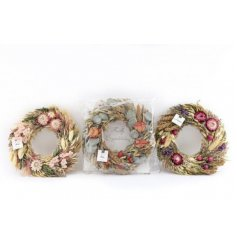 An assortment of beautifully decorated round wreaths, made up of dried plants and grasses