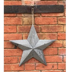 A large sized natural wooden star set with a rustic finish and a chunky rope hanger