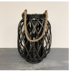 A dark toned woven wicker lantern with a chunky rope handle accent and glass insert