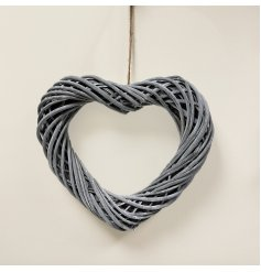A woven wicker wreath in a heart shape set with a smooth grey toned finish