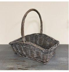 A high quality woven wicker picnic basket set with a tall traditional woven handle and rustic finish