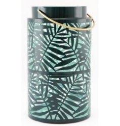 Set with a bold olive green tone and added gold handle, this metal lantern also features a cut out leaf design