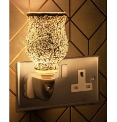 A plug in powered Desire Aroma Dispenser with a beautiful mosaic silver decal and soft glow