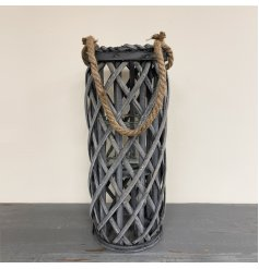 A large grey woven wicker lantern with a chunky rope handle accent and glass insert