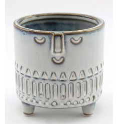 Sure to add some character charm to your interior decor, a smooth glazed decorative pot with an embossed face decal