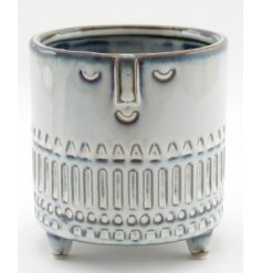 A smooth glazed pot with added embossed features and a smiling face