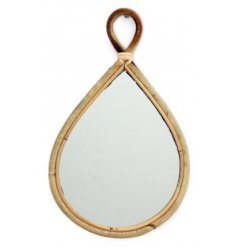 A large tear drop shaped mirror with a curved rattan framing