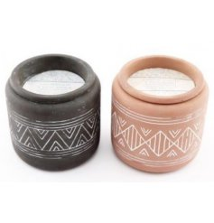 An assortment of terracotta based candles, each set with am embossed Aztec inspired print