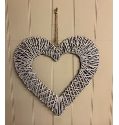 A large decorative hanging wicker heart with a cut out centre and soft grey tone to finish