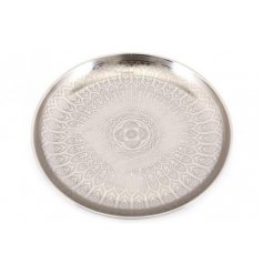 A large round metal plate featuring a gorgeously intricate embossed detailing