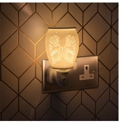 A plug in powered Desire Aroma Dispenser with a stunning Angel Wing decal and warming glow