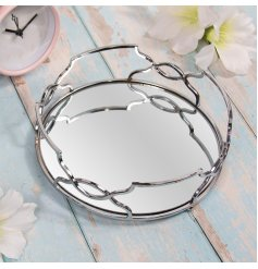 A gorgeously sleek and simple round metal tray featuring a Gatsby inspired edging and mirrored centre