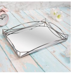 A gorgeously sleek and simple rectangular metal tray featuring a Gatsby inspired edging and mirrored centre