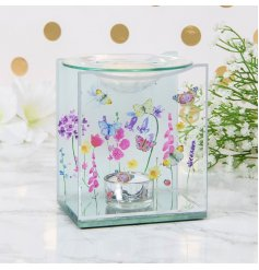 A delicately designed glass oil burner set with a mirrored backing and pretty floral decals surrounding it