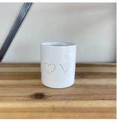 A simplistic white toned ceramic candle pot featuring a pierced LOVE text decal
