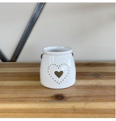 A small ceramic T-light featuring a sleek white tone and pierced dotted heart decal to the front