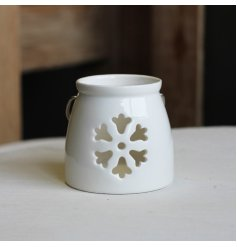 A small ceramic T-light holder featuring a snowflake shaped cut decal