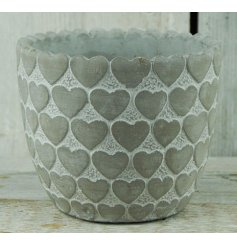 A small cement pot featuring a heart scalloped edge, added surrounding heart print and white washed finish