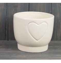 A small ceramic pot featuring a smooth cream finish and subtle embossed heart design