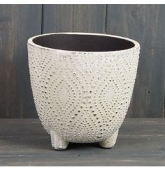 A small offwhite toned pot featuring based feet and a pretty dotted decal with a rustic touch