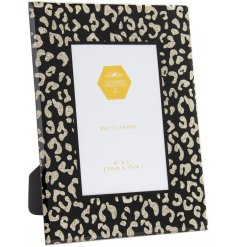 Add a glittery hint to any home space as well as a wild touch with this sleek black glass frame with gold glitter accent