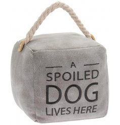 A square shaped doorstop set with a grey faux fur covering and stitched Dog script text to finish