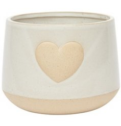 A chunky ceramic planter with a smooth off white tone and embossed heart centre