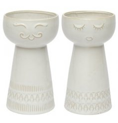 An assortment of decorative vases with embossed facial decals to each