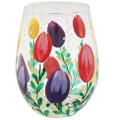 A sleek stemless glass featuring a gorgeous display of multi toned tulips, beautifully hand painted