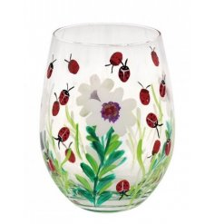 A stemless glass decorated with a delightful hand painted flower and ladybird print
