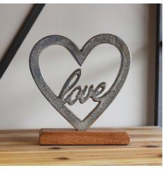 Set upon a natural wood block base, this heart ornament is perfect for bringing to any home space
