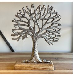 A large ornamental silvered tree decoration placed on top a natural wooden block