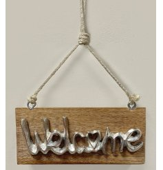 A small and simple natural wooden block plaque featuring a rustic metal welcome text decal