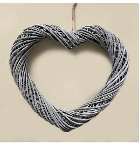 An extra large sized woven wicker heart hung from jute string, make your own by adding lights and foliage