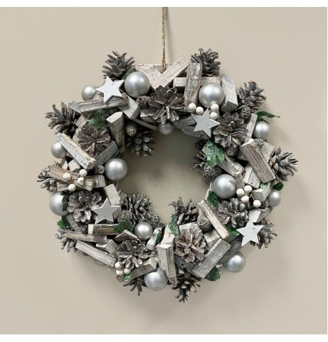 A beautifully rustic wreath with artificial foliage, pinecones, silver baubles and stars