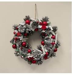 A large decorative wooden wreath with added bold red tones and festive accents