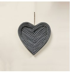 A grey toned hanging heart shaped wreath, set with patterned twigs for a trending look