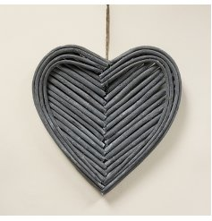 A grey toned heart shaped wreath made from natural twigs that form a patterned centre