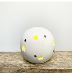 A stylishly simple round ceramic ball decoration set with gold dots and a warm glowing LED centre